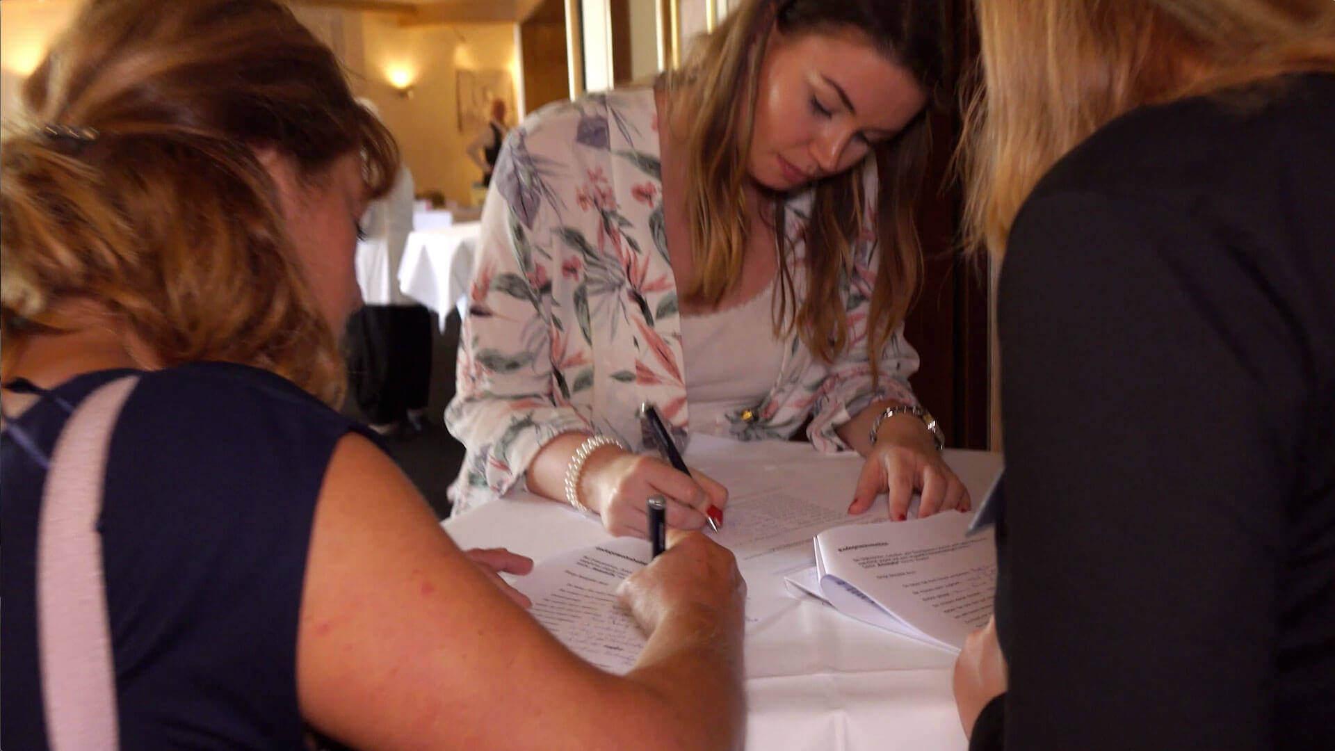 Workshop Teilnehmerinnen beim ausfüllen von Weiterbildungsunterlagen